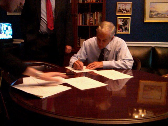 Ron Paul signs copies of the Industrial Hemp Farming Act, which is printed on hemp paper.